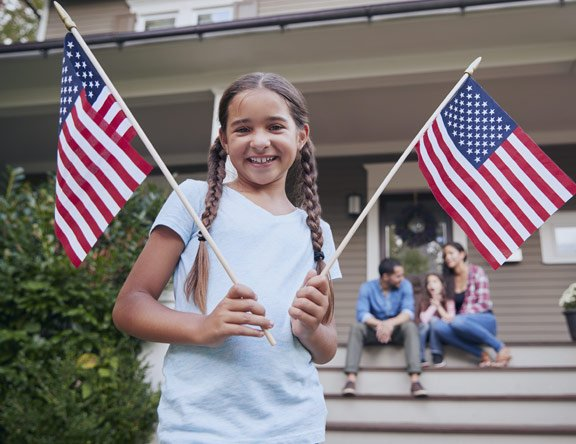 Family sitting in front of house holding USA flag