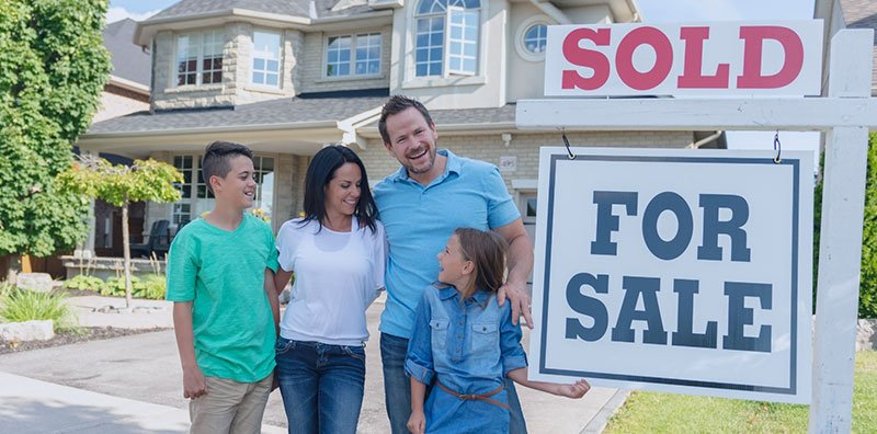 family next to a for sale/sold sign